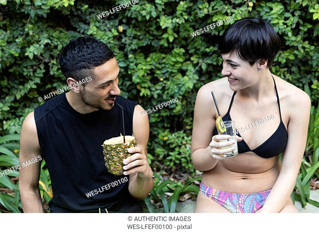 Smiling couple flirting having a cocktail outside