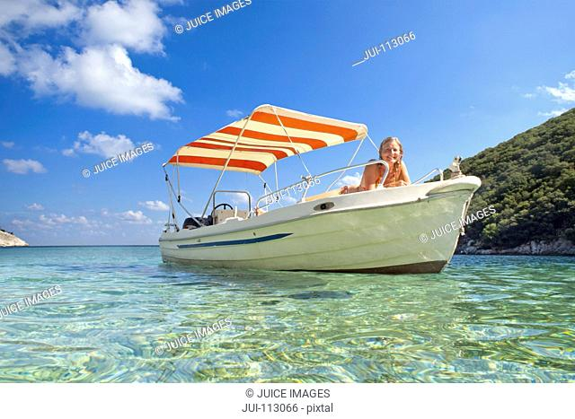 Portrait smiling woman sunbathing on boat in ocean