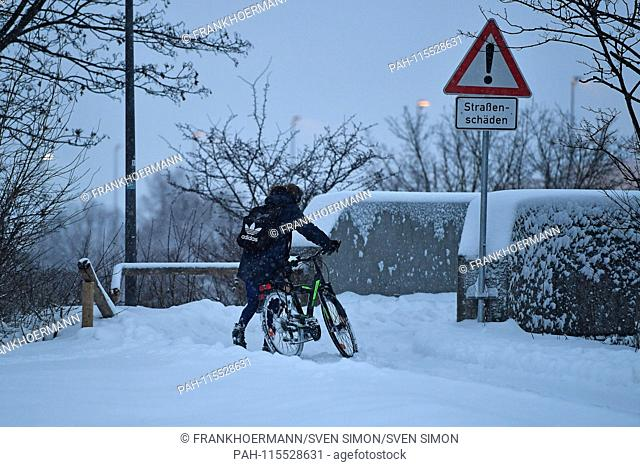 Snow chaos on Bavaria's streets - this cyclist pushes his bike on a snow-covered, snow-covered bike path. Continuing snowfall on 10.01