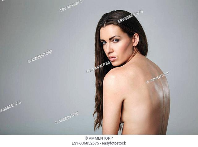 Beautiful naked woman looking at camera. Nude female model against grey background with copy space