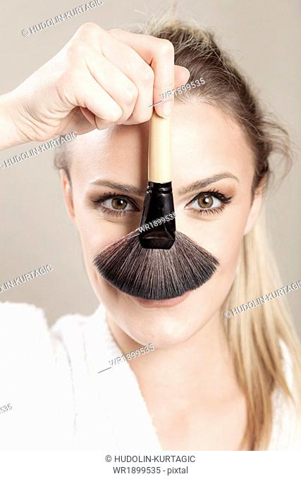 Young woman holding makeup brush