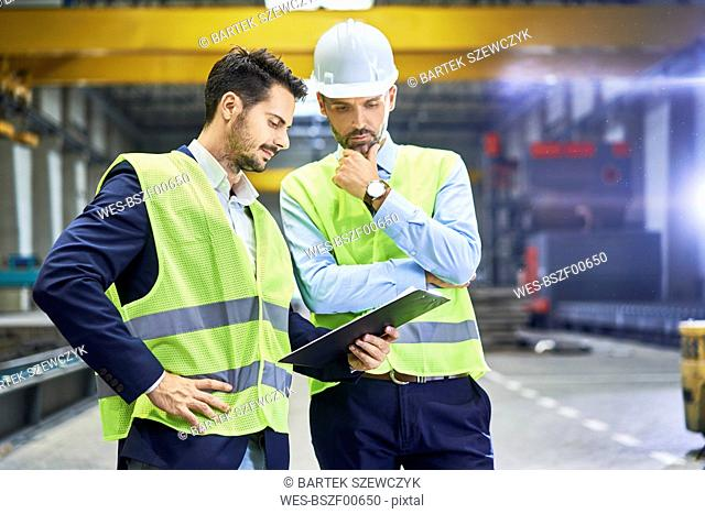 Two managers wearing protective workwear looking at clipboard in factory