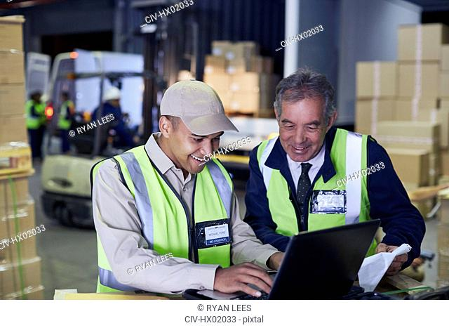 Manager and worker using laptop at distribution warehouse loading dock