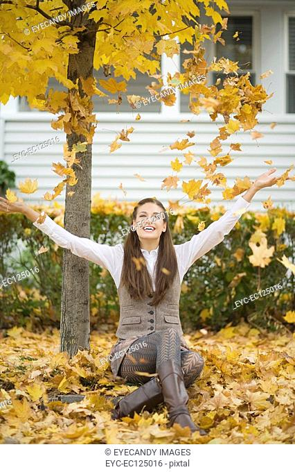 Portrait of young happy woman playing in autumn leaves
