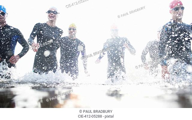 Triathletes in tri suits running in waves