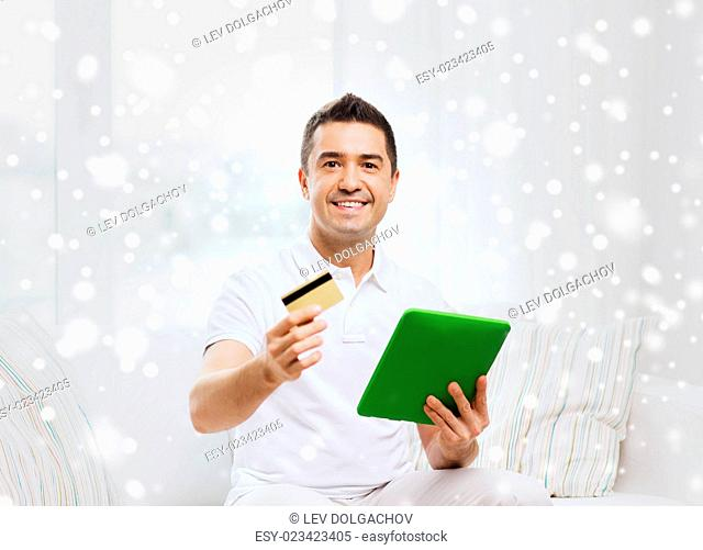 technology, people and lifestyle, distance learning concept - happy man working with tablet pc computer at home over snow effect