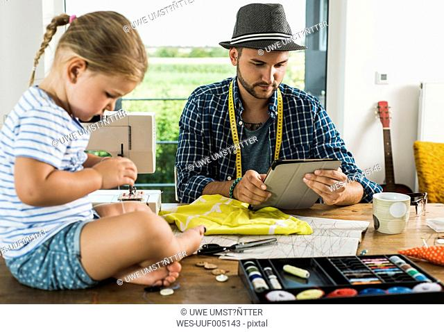 Father with digital tablet and daughter sewing at home