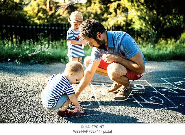 Father drawing Hopscotch on asphalt