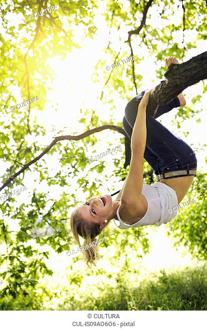 Young woman hanging upside down and holding onto tree branch