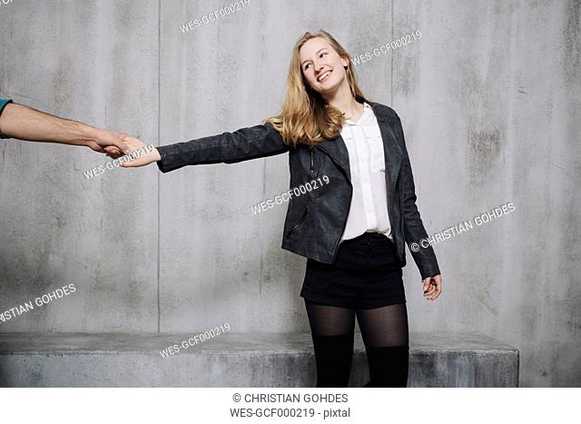 Couple in front of concrete wall, woman holding hand of man