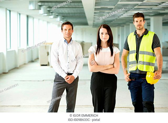 Portrait of three workers, standing in newly constructed office space