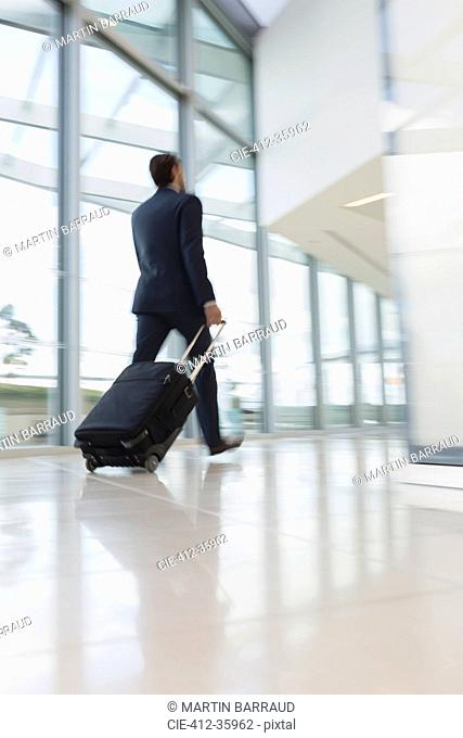 Businessman walking, pulling suitcase in airport