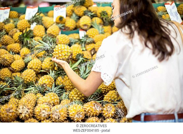 Woman checking pineapples at fruit stall