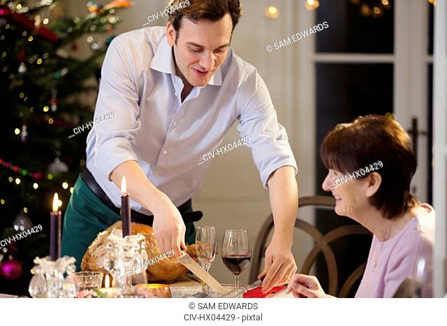 Son serving Christmas turkey to senior mother at candlelight dinner table