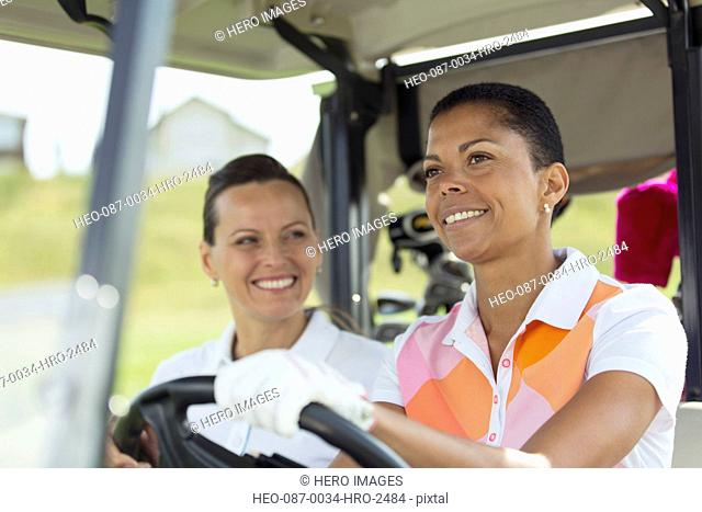middle-aged female golfers smiling in golf cart