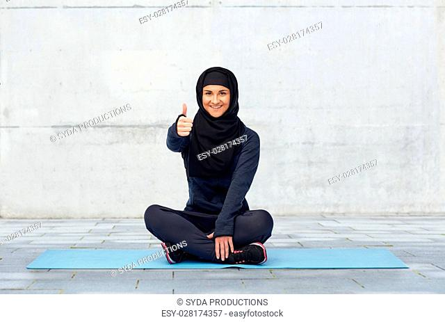 sport, fitness and people concept - happy smiling muslim woman in hijab sitting on mat and showing thumbs up over urban concrete background