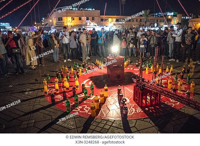 Group of people playing fishing-pole game with soda pop bottle in Jemaa el-Fnaa square at night, Marrakesh, Morocco