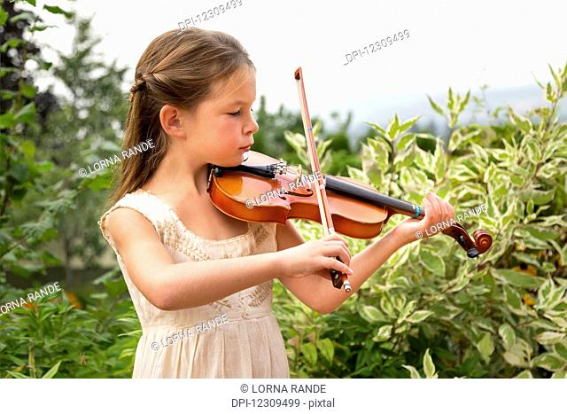 A young girl playing a violin in her yard; Salmon Arm, British Columbia, Canada