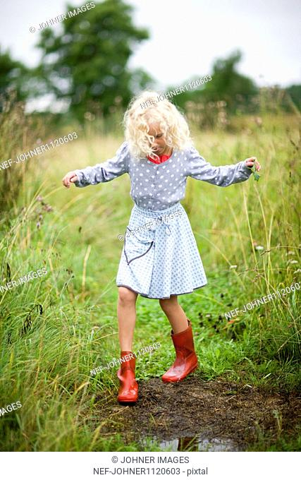Girl wearing boots standing by puddle