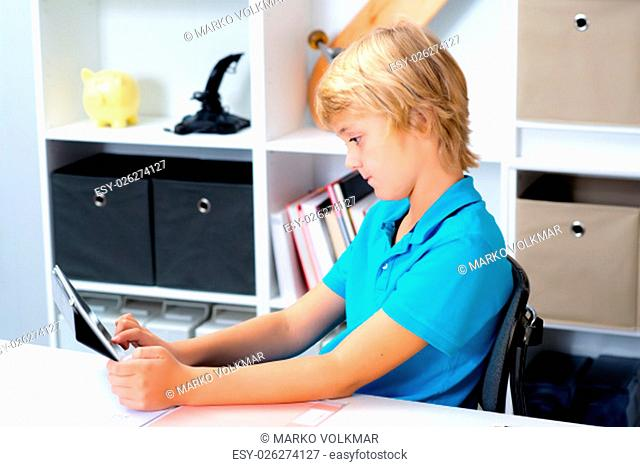 blond boy using tablet computer in his room