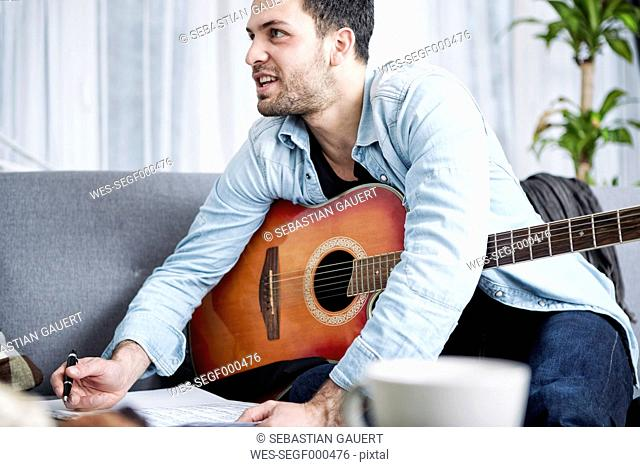 Young man with guitar composing a song