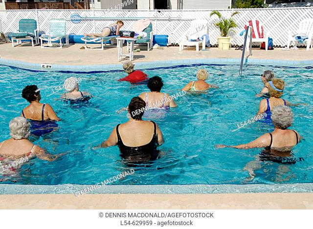 Adult senior females engage in aquatic water exercises for fitness and pleasure Ruskin Florida