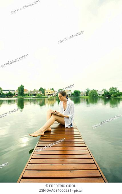 Woman sitting on lake dock using digital tablet