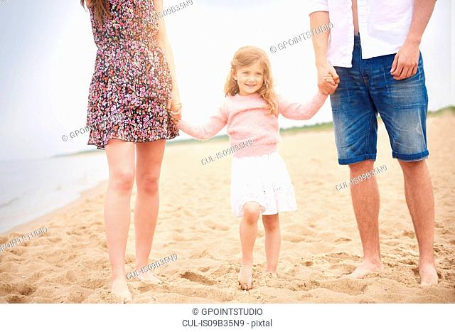 Family holding hands walking on beach