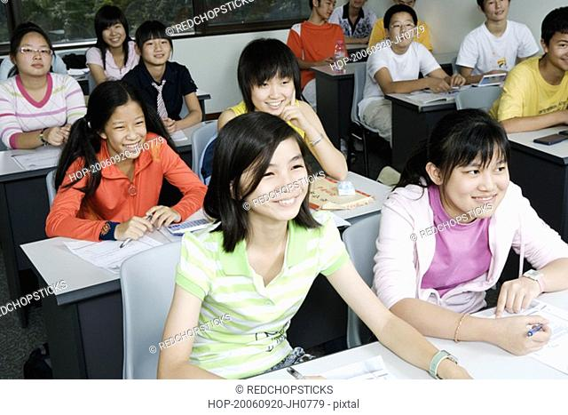 Group of teenage boys and teenage girls sitting in a classroom and smiling