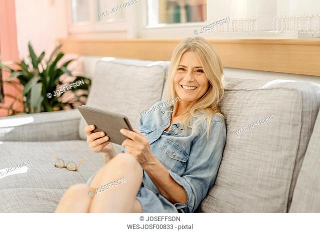 Smiling woman at home on couch with tablet
