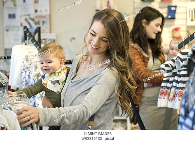 Caucasian mother and baby son shopping in clothing store