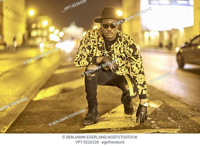 fancy blogger man crouching at city street at night, wearing stylish outfit, car lights, traffic, cool attitude, at Ludwigstraße in Munich, Germany