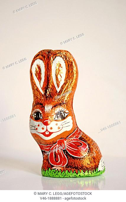 Chocolate Easter Bunny wrapped in red foil with cartoon eyes and big ears  Bunny has freckles and big eyelashes  White mouth and large red bow on the foil...