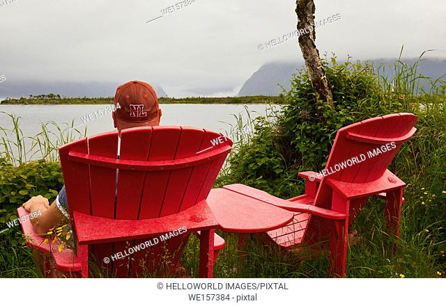 Rear view of male tourist wearing a Newfoundland cap relaxing next to Western Brook Pond, a lake fjord amongst the Long Range Mountains in the Gros Morne...