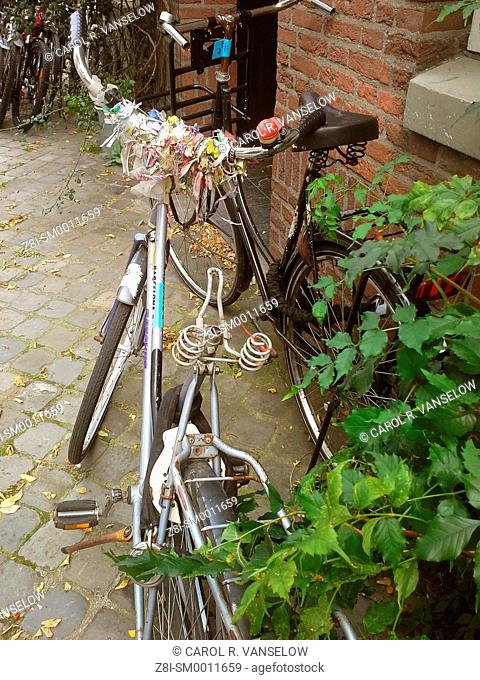 Bicycle with many coloured ribbons on handlebars, but no seat. Photo is taken in Maastricht, the Netherlands