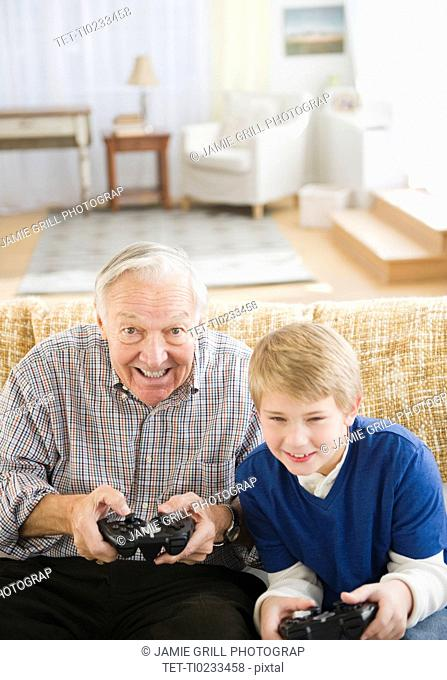 Grandfather and grandson 8-9 playing video games