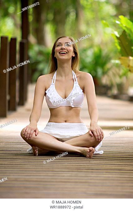Young woman in bikini sits on a boardwalk, cross-legged, Lankayan Island, Borneo, Malaysia