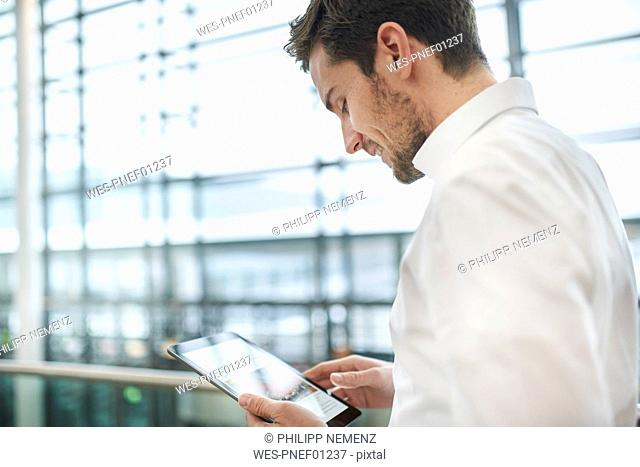 Smiling young businessman using tablet