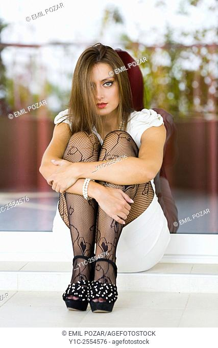 Stock Photo - Young woman fashionable embracing legs
