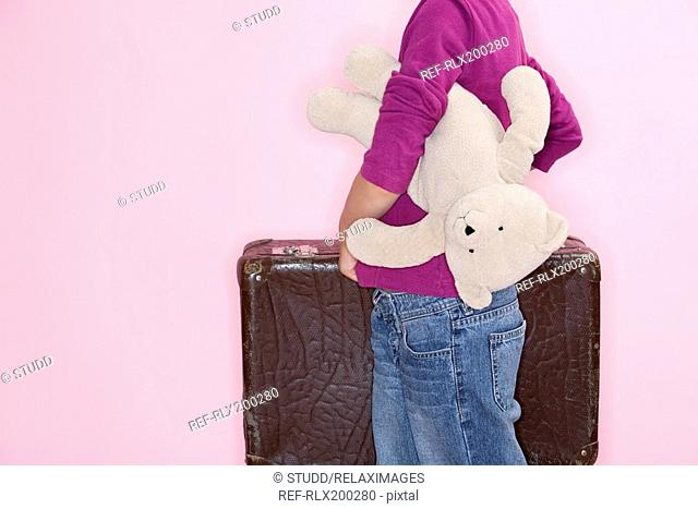 Girl 8 holding suitcase and Teddy Munich, Bavaria, Germany