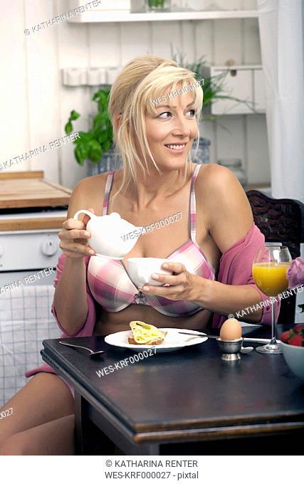 Germany, Munich, Mature woman having breakfast in kitchen