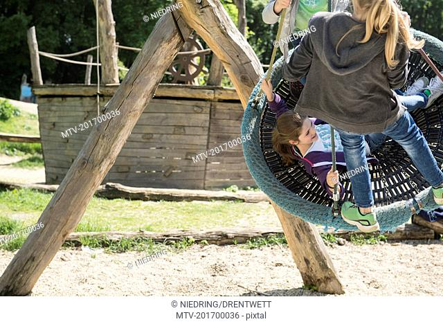 Two girls swinging on a swing in playground, Munich, Bavaria, Germany