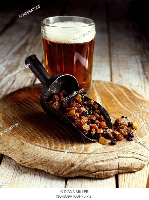 Still life of raisins in scoop with glass of ale