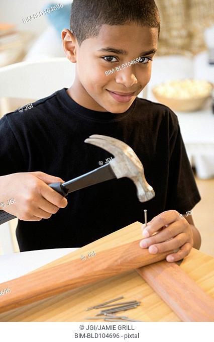 Hispanic boy using hammer and nails