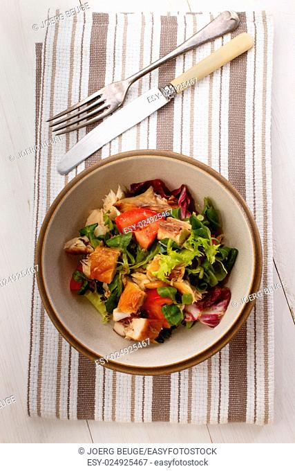 smoked scottish mackerel salad with tomato and chopped onion in a bowl