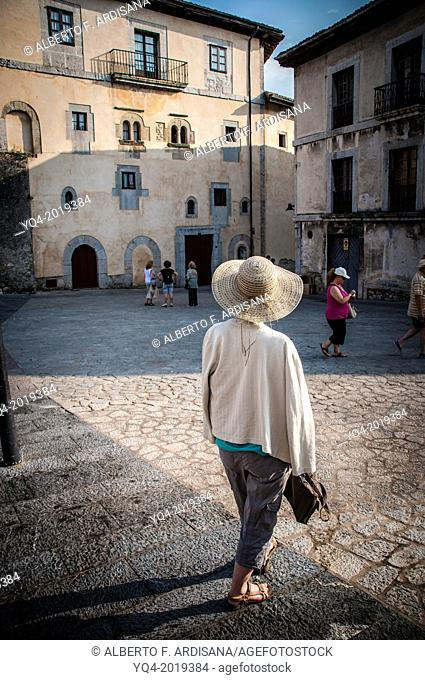 A woman with hat, wander through the old town of Llanes. Asturias, Spain