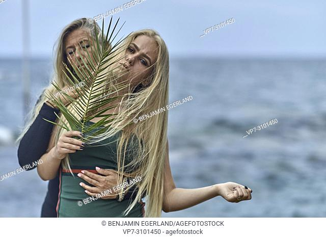 mother (43 years) with teenage daughter (13 years) behind leaf, thoughtful, back to nature, relaxed, togetherness. Danish ethnicity