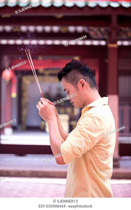 A Chinese man is praying outside a Buddhist temple and burning incense. Asian man praying in a temple