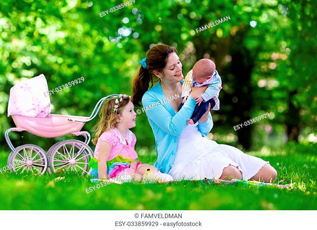 Family with children enjoying picnic outdoors. Mother with newborn baby and toddler child relax in a park. Little girl playing with toy stroller