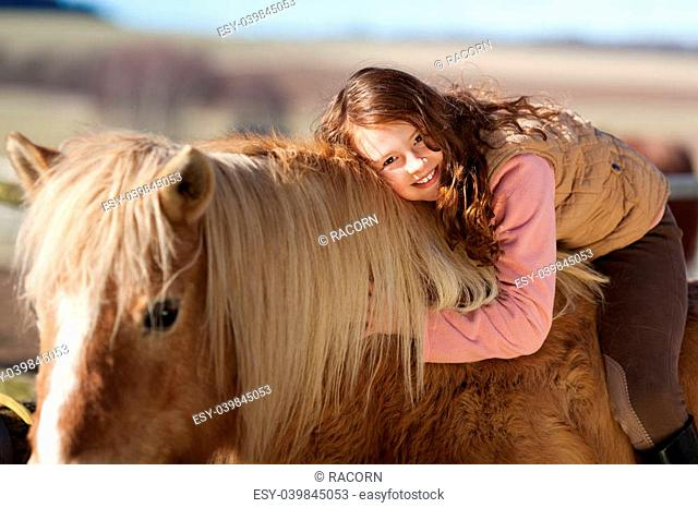 Smiling young girl out riding leaning forwards over the neck of her horse to pet and cuddle it in a show of affection